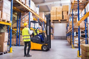 Woman in high vis man on fork lift truck in warehouse