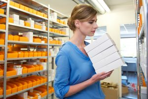 Female pharmacist storing medicines on shelves