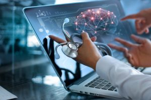 Doctor holding a stethoscope looking at brain activity on laptop