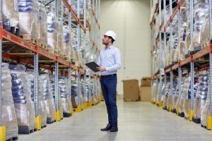 Man in hard hat checking off stock in factory warehouse